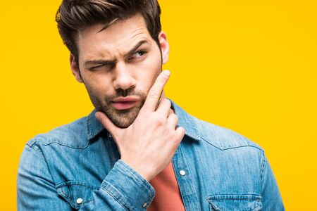 Confused handsome man touching chin isolated on yellow background Stock fotó