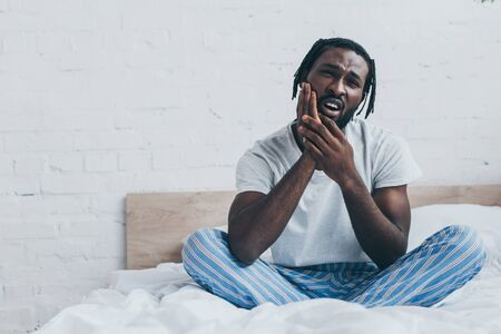 Handsome African American man in pajamas suffering from tooth pain in bedroom