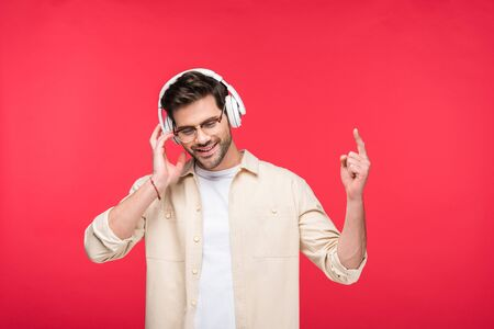 Smiling handsome man in headphones pointing with finger isolated on pink background