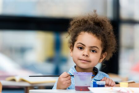 Selective focus of cheerful African American child looking at camera and holding paintbrush