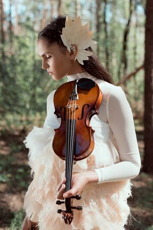 Tender woman in white swan costume standing on forest background with violin, looking away