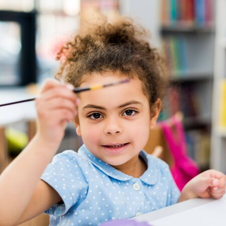 Selective focus of cheerful African American kid holding paintbrush Stock Photo