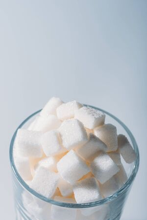 White sweet sugar cubes in glass on grey background Stockfoto - 125563458