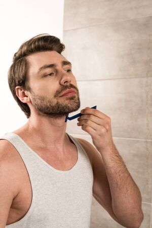 Handsome man shaving beard with razor in bathroom