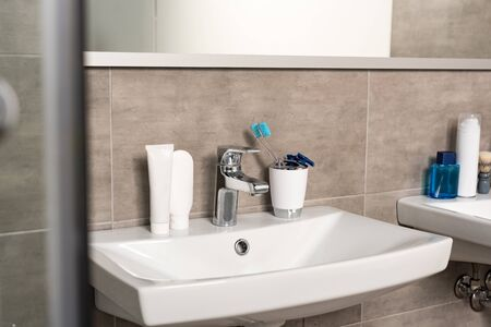 Toothbrushes, toothpaste and shaving razors on sink in bathroom