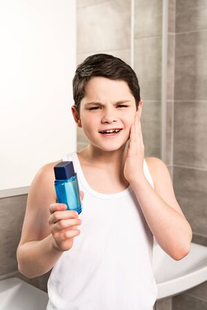 Dissatisfied preteen boy applying lotion on face and looking at camera in bathroom
