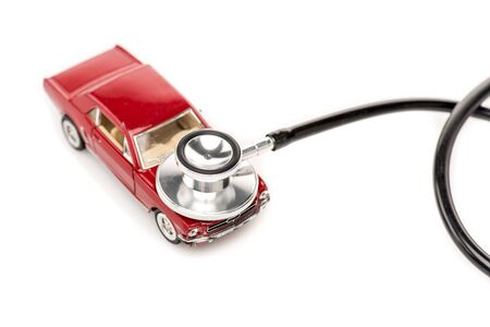 Red toy car and stethoscope isolated on white background surface