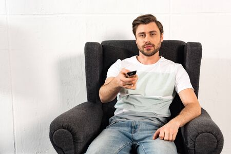 Man in jeans sitting in armchair and holding remote controller