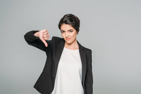 Displeased mixed race businesswoman showing thumb down while looking at camera isolated on grey background Foto de archivo - 126160907