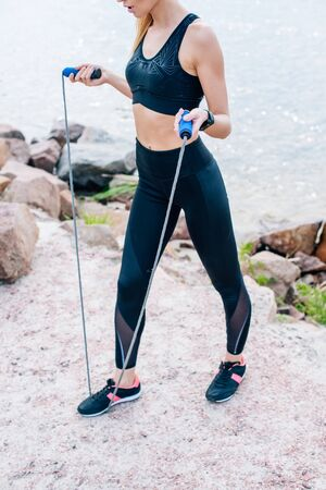 Cropped view of young woman in sportswear standing and holding jump rope Banco de Imagens