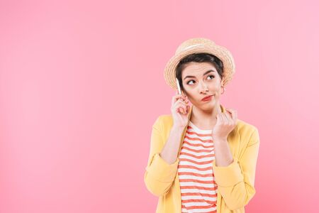 Skeptical mixed race woman in straw hat looking away isolated on pink background