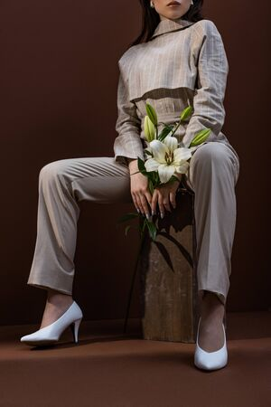 Low angle view of fashionable woman with flower in hands sitting on box