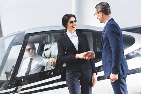 Businesspeople in suits shaking hands near helicopter with pilot