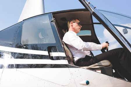Good-looking Pilot in sunglasses and formal wear sitting in helicopter cabin Stok Fotoğraf