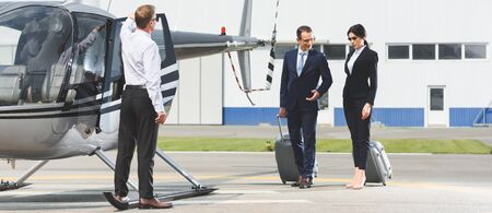 Panoramic shot of business partners with luggage near pilot and helicopter