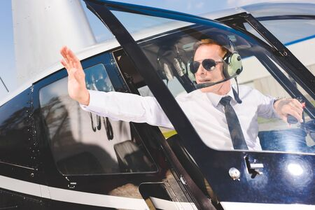 Pilot in sunglasses and headset sitting in helicopter cabin and showing stop sign Stok Fotoğraf