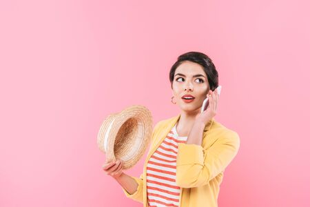 Pretty mixed race woman talking on smartphone and holding straw hat isolated on pink background