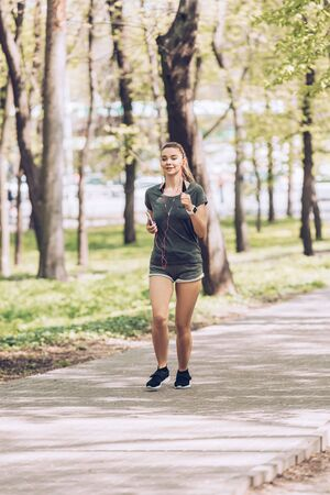 Pretty young woman holding smartphone and listening music in earphones while running in park