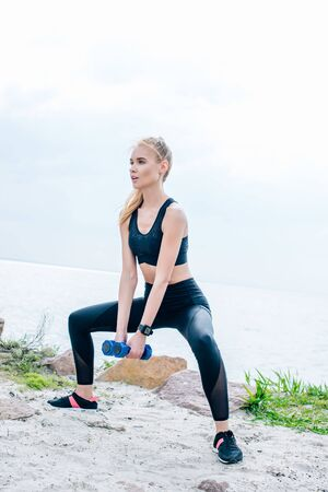 Attractive blonde young woman exercising with blue dumbbells Фото со стока