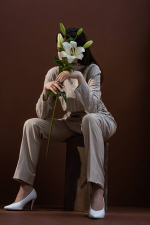 Low angle view of adult model holding flower near face, sitting on brown background 写真素材