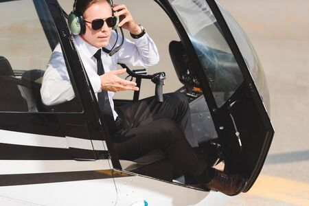 Mature Pilot in sunglasses and headphones gesturing and sitting in helicopter cabin