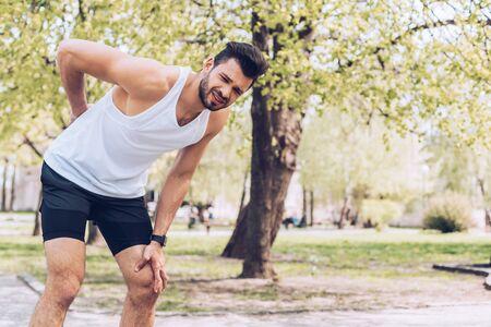 Homme bouleversé en tenue de sport touchant le dos blessé et souffrant de douleur