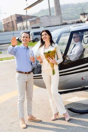 Happy husband and wife with flowers on romantic date near helicopter