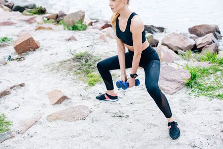 Cropped view of young woman exercising with dumbbells near stones