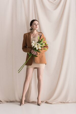 Trendy model in beige dress and blazer standing on curtain background with flowers Stok Fotoğraf