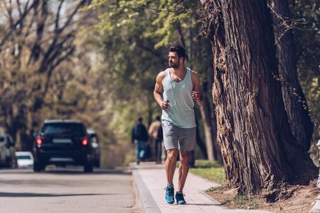 Handsome sportsman running along pavement near roadway and listening music in earphones. Stock Photo