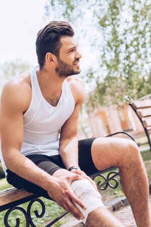 Injured sportsman looking away while sitting on bench and touching elastic bandage on knee Archivio Fotografico - 126202256