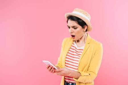 Shocked mixed race woman in bright clothing and straw hat using smartphone isolated on pink background