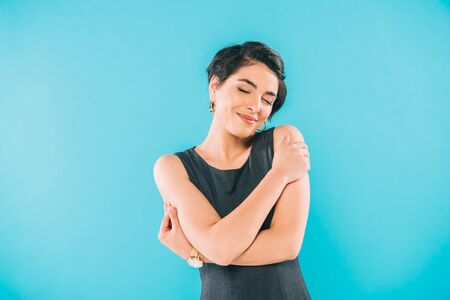 Beautiful mixed race woman posing at camera with closed eyes isolated on blue background