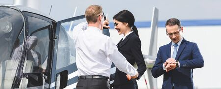 Panoramic shot of businesspeople in formal wear near helicopter and Pilot