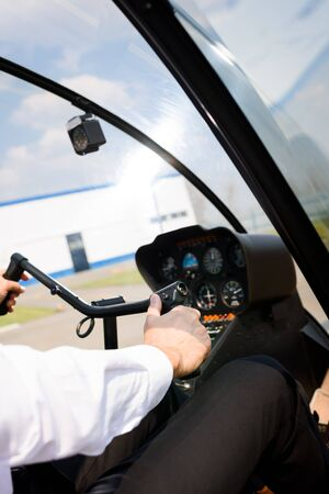 Cropped view of Pilot in formal wear sitting in helicopter cabin and holding wheel