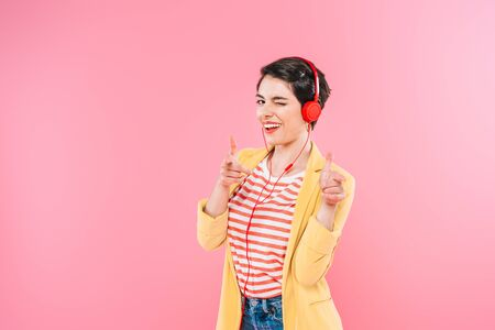 Cheerful mixed race woman listening music in headphones, pointing with fingers and winking at camera isolated on pink background Banco de Imagens