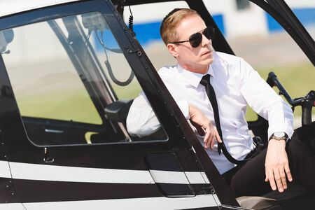 Serious mature Pilot in formal wear sitting in helicopter cabin