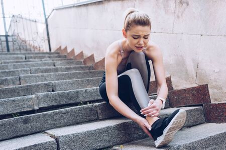 Attractive sportswoman sitting on stairs and suffering from pain while touching injured leg