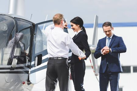 Businesspeople in formal wear near helicopter and Pilot