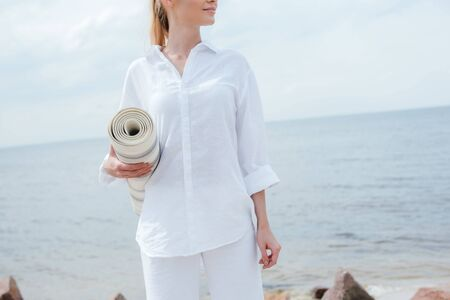 Cropped view of happy young woman standing near sea and holding yoga mat