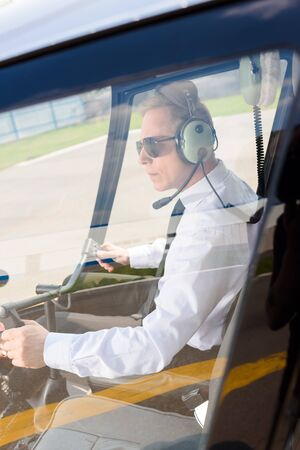 Mature Pilot in sunglasses and headphones with microphone sitting in helicopter cabin