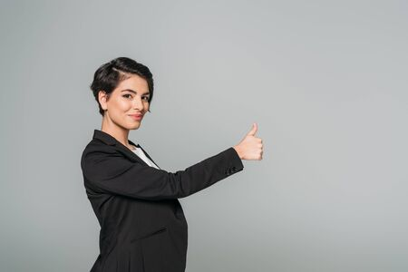 Smiling mixed race businesswoman showing thumb up and looking at camera isolated on grey background