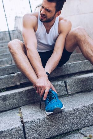 Upset sportsman suffering from hurt while sitting on stairs and suffering from pain 스톡 콘텐츠
