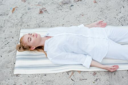 Overhead view of attractive blonde woman with closed eyes meditating while lying on yoga mat