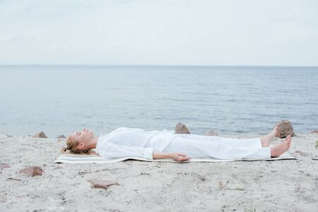 Attractive blonde woman with closed eyes meditating while lying on yoga mat near sea