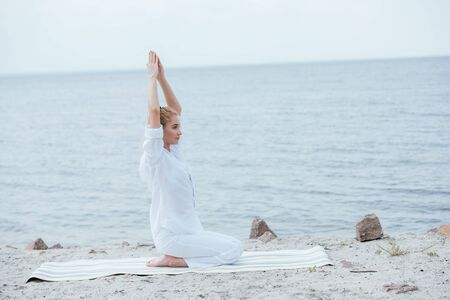 Attractive blonde woman practicing yoga with hands above head near river