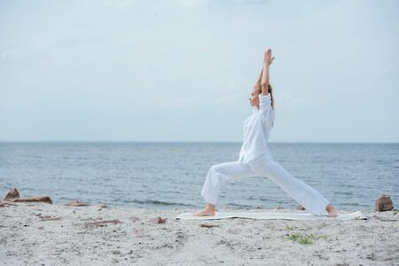 Side view of blonde woman practicing yoga near river Фото со стока