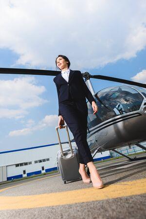 Flachwinkelansicht der Geschäftsfrau in formeller Kleidung mit Koffer in der Nähe des Hubschraubers