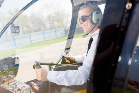 Mature Pilot in sunglasses and headphones with microphone smiling while sitting in helicopter cabin