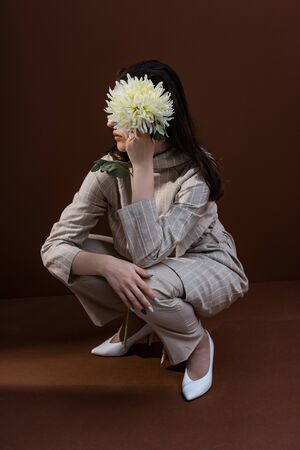 Beautiful and stylish model holding chrysanthemum near face, sitting on brown background 写真素材